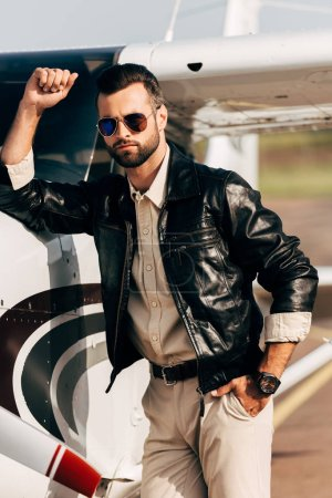 serious fashionable male pilot in leather jacket and sunglasses standing near airplane