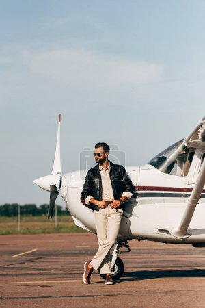 handsome man in leather jacket and sunglasses posing near airplane