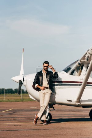 stylish male pilot in leather jacket and sunglasses posing near aircraft