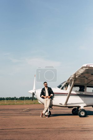 fashionable male pilot in leather jacket and sunglasses posing near plane
