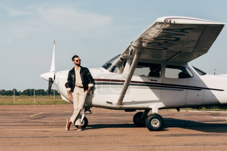 young fashionable male pilot in leather jacket and sunglasses posing near plane