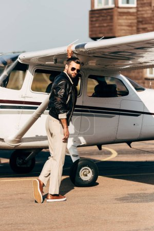 handsome stylish male pilot in leather jacket and sunglasses standing near aircraft