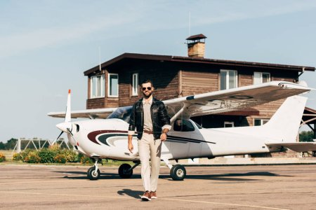 fashionable young male pilot in leather jacket and sunglasses walking near airplane