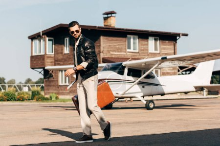 stylish young man in leather jacket and sunglasses walking with suitcase near airplane