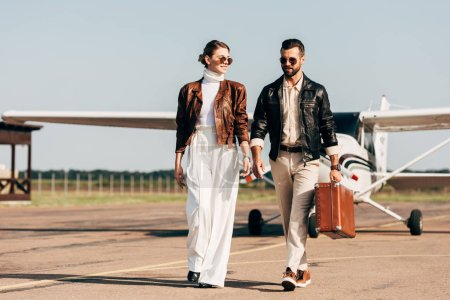 Photo for Happy young couple in leather jackets and sunglasses walking with retro suitcase near airplane - Royalty Free Image