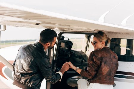 rear view of young man in leather jacket helping girlfriend boarding in airplane