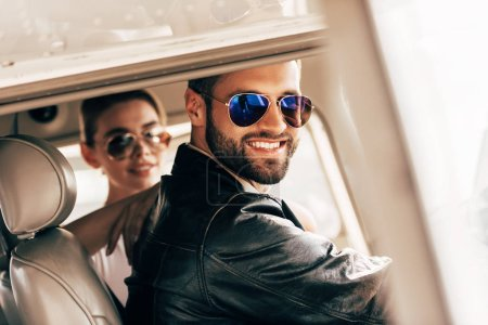 happy male pilot in sunglasses and leather jacket looking at camera while his girlfriend sitting near in cabin of airplane