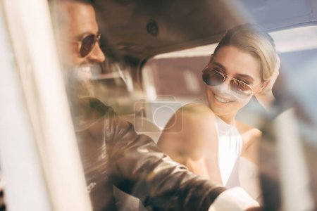 selective focus of happy male pilot in sunglasses and leather jacket sitting with girlfriend in cabin of airplane