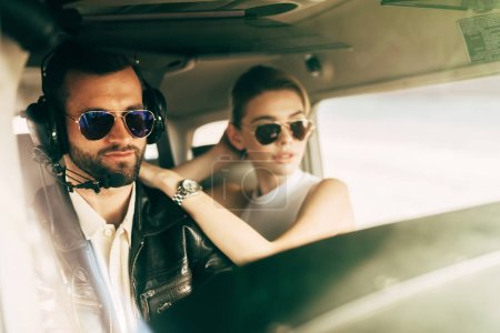 handsome male pilot in headset and sunglasses sitting with girlfriend in cabin of airplane