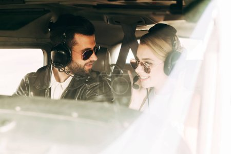 male pilot in headset and sunglasses talking to girlfriend in cabin of airplane