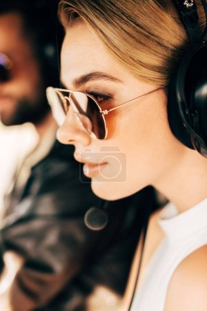 selective focus of beautiful woman in sunglasses and headset sitting near male pilot in cabin of airplane