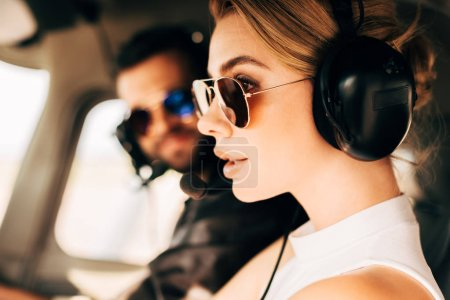 side view of attractive woman in sunglasses and headset sitting near male pilot in cabin of airplane