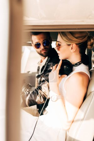 side view of serious male pilot in sunglasses sitting with girlfriend in cabin of airplane