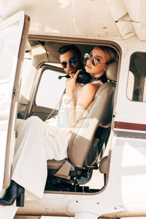attractive young woman in sunglasses and headset over neck sitting near boyfriend in cabin of airplane