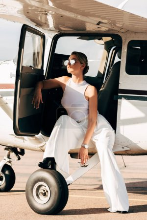 young fashionable woman in sunglasses sitting near airplane