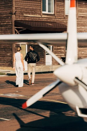 rear view of young woman walking with boyfriend in leather jacket near airplane