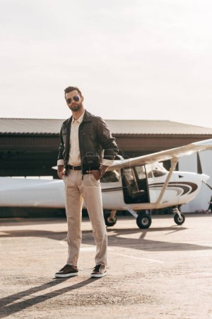 serious male pilot in leather jacket and sunglasses posing near airplane