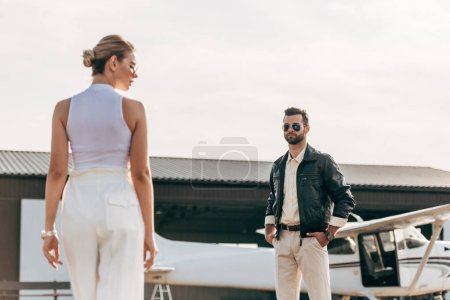 confident young man in leather jacket and sunglasses looking at girlfriend near airplane