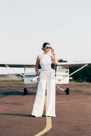 attractive stylish young woman in sunglasses looking away and posing near airplane