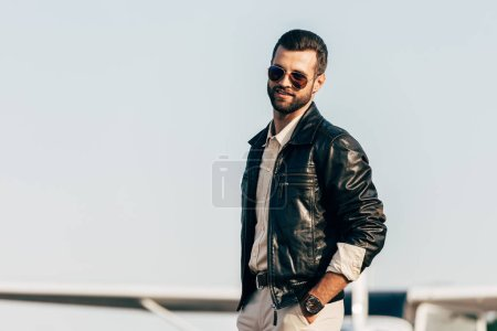 young handsome male pilot in leather jacket and sunglasses posing near airplane