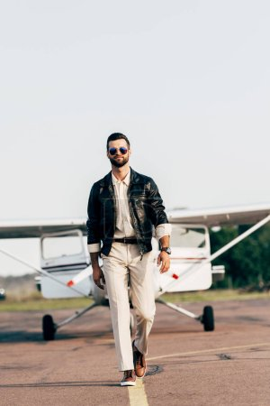 handsome male pilot in leather jacket and sunglasses walking near aircraft
