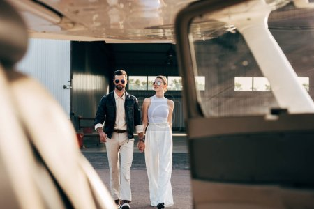 selective focus of stylish man in leather jacket and sunglasses walking with girlfriend near airplane