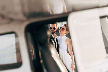 selective focus of handsome man in leather jacket and sunglasses standing with girlfriend near plane