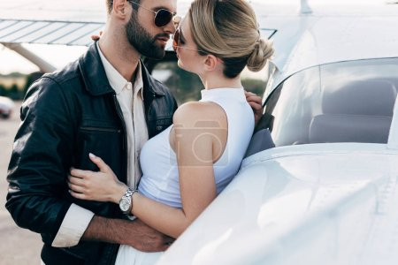 Photo for Handsome young man in leather jacket and sunglasses embracing girlfriend near plane - Royalty Free Image