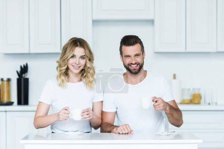 Photo for Happy young couple holding cups of coffee and smiling at camera - Royalty Free Image