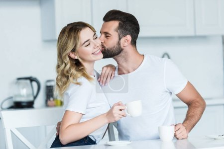 handsome bearded man kissing smiling girlfriend while drinking coffee together