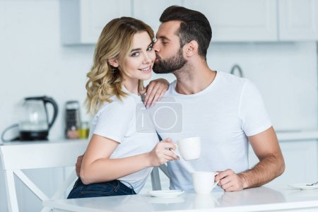 Photo for Handsome young man kissing beautiful girlfriend smiling at camera while drinking coffee together - Royalty Free Image