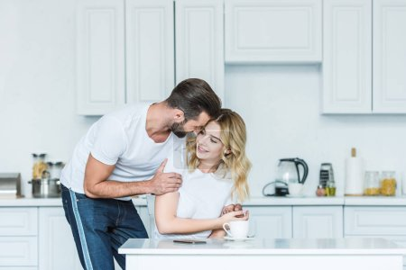 happy young couple embracing during breakfast in kitchen