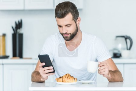 handsome bearded young man using smartphone during breakfast