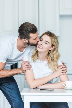 handsome young man kissing smiling girlfriend at morning
