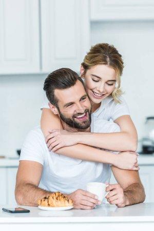 Foto de Mujer joven feliz abrazando la taza de explotación novio sonriente de café por la mañana - Imagen libre de derechos