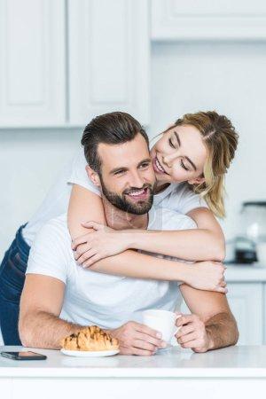 beautiful smiling young woman hugging happy boyfriend during breakfast