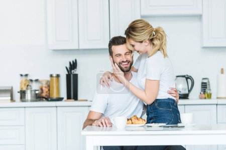attractive smiling girl hugging happy boyfriend while having breakfast together