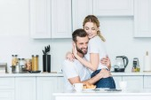 beautiful happy young couple in love hugging during breakfast in kitchen