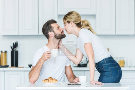 beautiful young couple in love able to kiss while having breakfast together