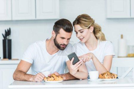 Photo pour Sourire de jeune couple à l'aide de smartphone tout en prenant son petit déjeuner ensemble - image libre de droit
