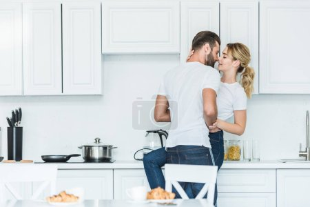 beautiful young couple in love kissing in kitchen at morning