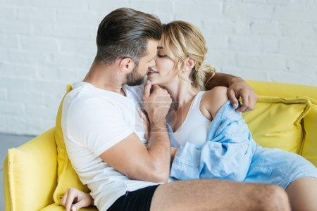 Photo pour Belle jeune couple heureux en amour, caresses et baisers sur canapé - image libre de droit