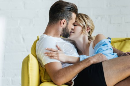 beautiful tender young couple in love kissing on couch