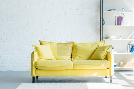 Photo for Cozy yellow sofa with cushions in living room interior - Royalty Free Image