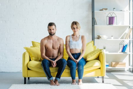 beautiful young couple in jeans sitting on sofa and looking at camera