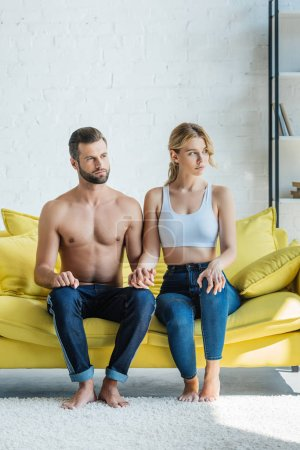 beautiful young couple holding hands and looking away while sitting together on yellow couch