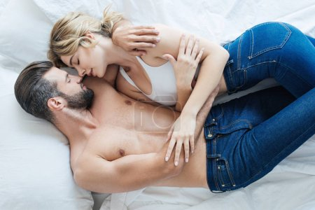 top view of seductive young couple in jeans hugging and lying together on bed