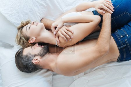top view of beautiful young couple in love hugging and lying together on bed