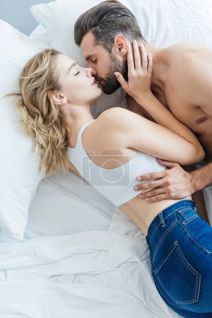 top view of beautiful young couple in love hugging and kissing in bed