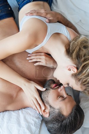 top view of beautiful seductive young couple able to kiss in bed